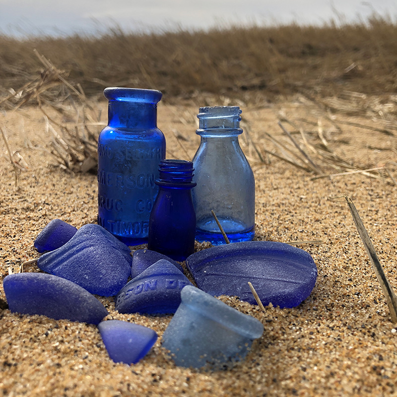 cobalt blue bottles and seaglass pieces in the sand